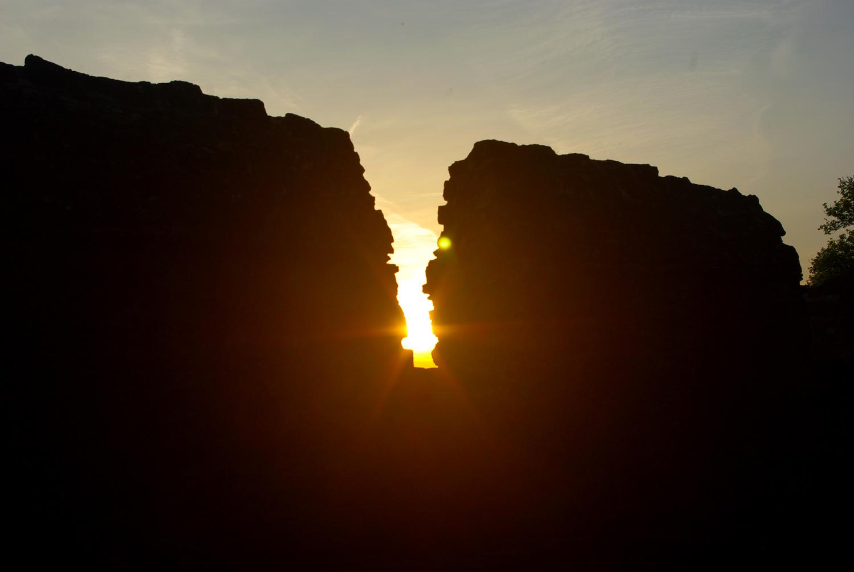 Die Sonne scheint zwischen Burgzinnen hindurch